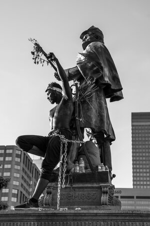 A performance artist that chained himself to a statue outside of the capitol building, raises his fist into the air.